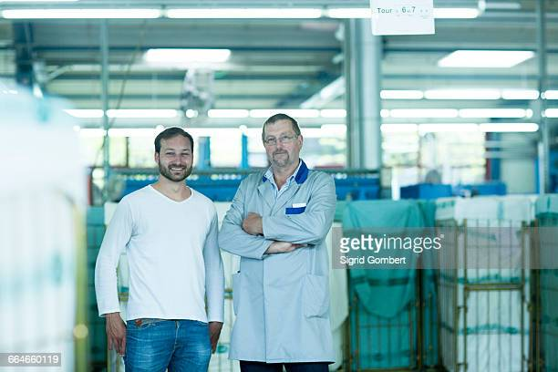 colleagues in launderette looking at camera smiling - sigrid gombert stock pictures, royalty-free photos & images