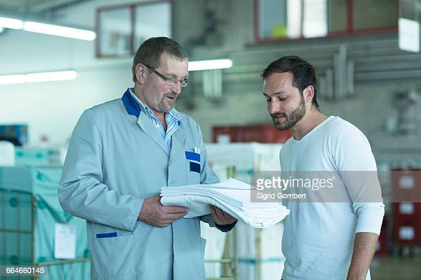 colleagues in launderette looking at laundry - sigrid gombert stock pictures, royalty-free photos & images