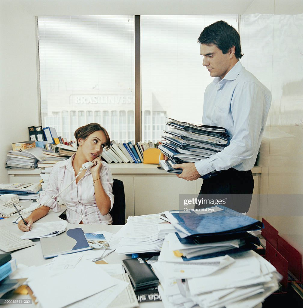 Messy Office: Colleagues In Messy Office Man Bringing Pile Of Papers To