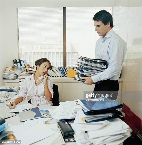 Colleagues in messy office, man bringing pile of papers to woman
