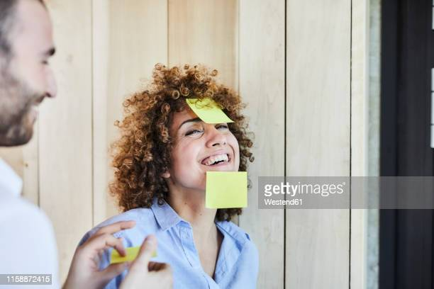 colleagues in office brainstorming and fooling around with post-its - inspiration stock-fotos und bilder