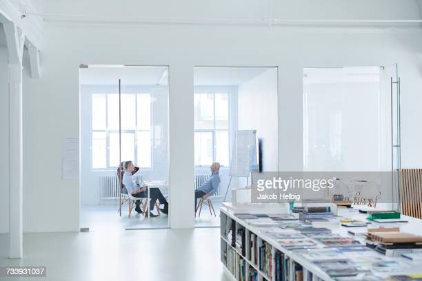 colleagues in office conference room in meeting - brightly lit stock pictures, royalty-free photos & images