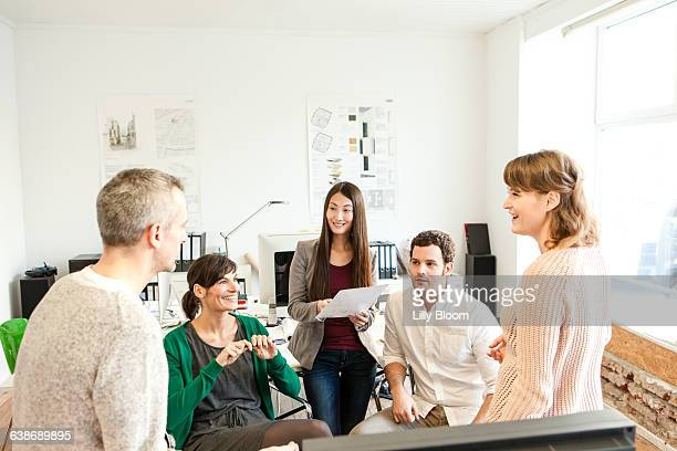 Colleagues in office discussing paperwork smiling