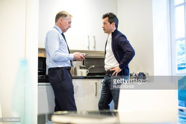 Colleagues in office kitchen having discussion