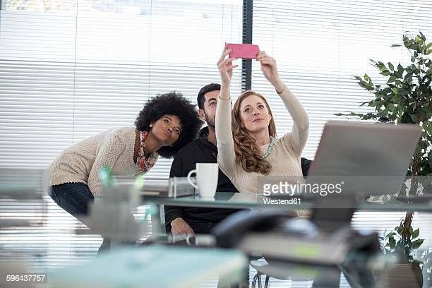Colleagues in office taking a selfie