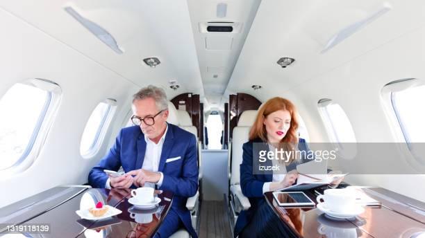kollegen im privatjet während der geschäftsreise - izusek stock-fotos und bilder