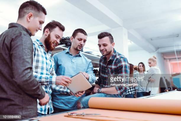 Kollegen In Textilfabrik neues Design auf Digital-Tablette zu prüfen