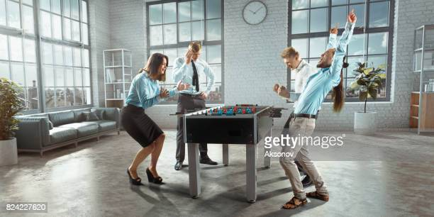 colleagues in the office play table football/kicker game. one team emotionally rejoices victory - face off sports play stock photos and pictures