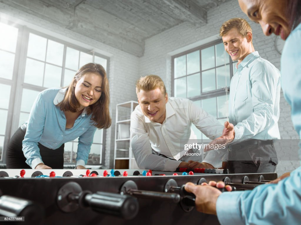 office play. Colleagues In The Office Play Table Football/kicker Game : Stock Photo