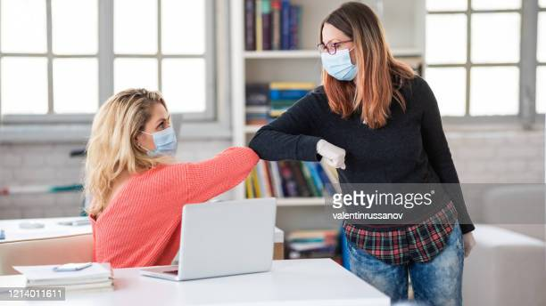colleagues in the office practicing alternative greeting for safety and protection during covid-19 - elbow bump stock pictures, royalty-free photos & images