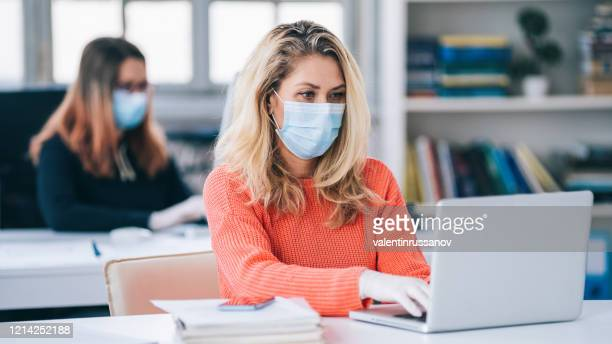 colleagues in the office working while wearing medical face mask during covid-19 - social distancing stock pictures, royalty-free photos & images