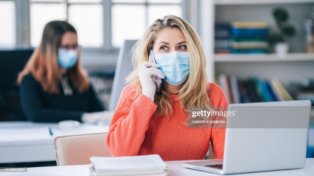 Colleagues in the office working while wearing medical face mask during COVID-19 : Stock Photo