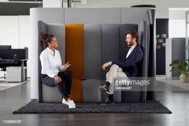 colleagues keeping distance while talking together in office - twee personen stockfoto's en -beelden
