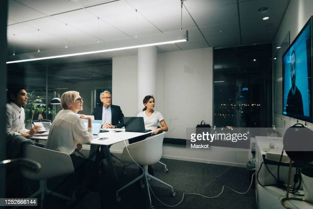 colleagues looking at businessman during video conference meeting at night in office - conference call stock pictures, royalty-free photos & images