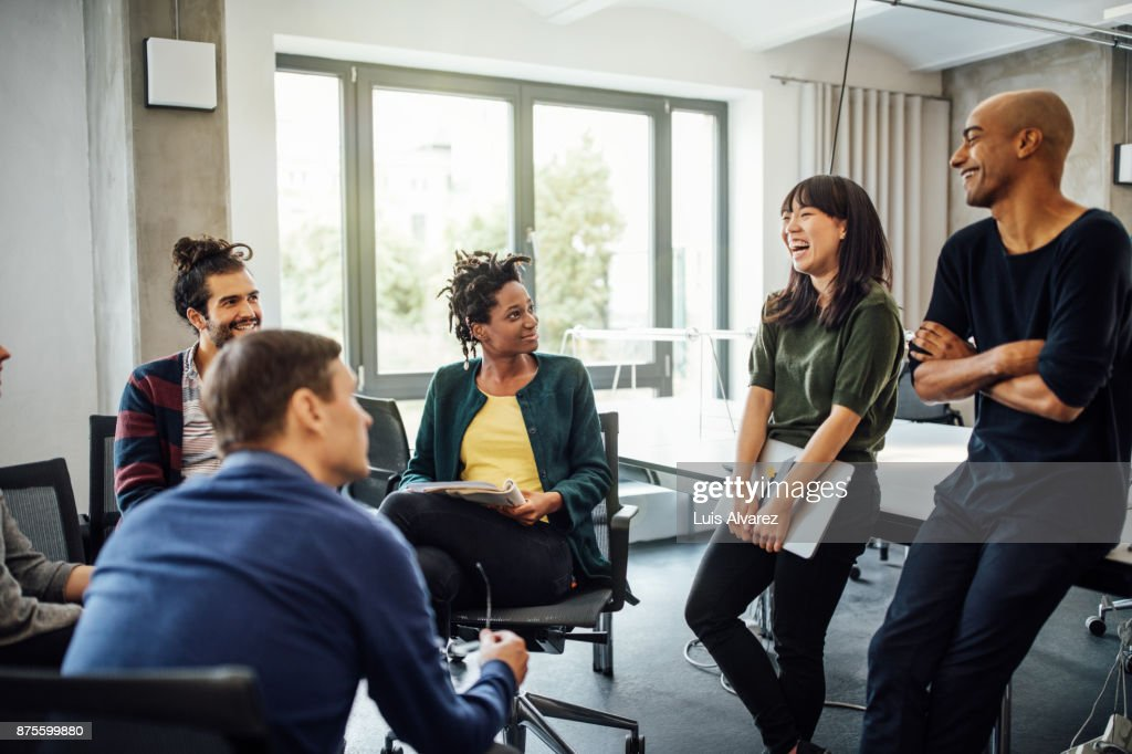 Colleagues looking at cheerful businesswoman in meeting : Stock Photo