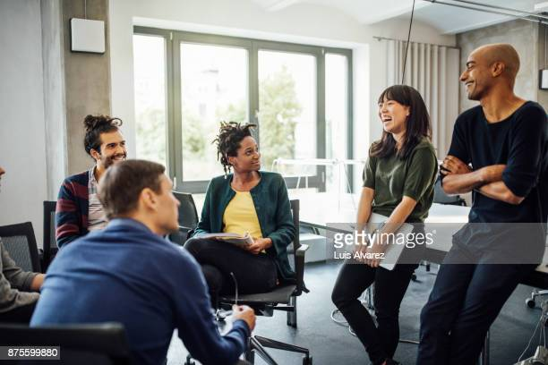 colleagues looking at cheerful businesswoman in meeting - multi etnische groep stockfoto's en -beelden