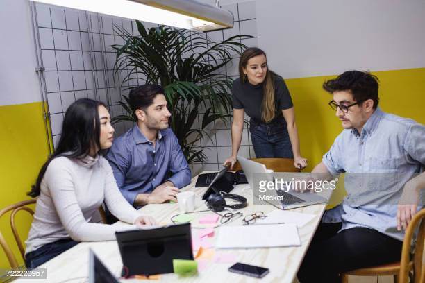 Colleagues looking at colleague using laptop during board room meeting in office