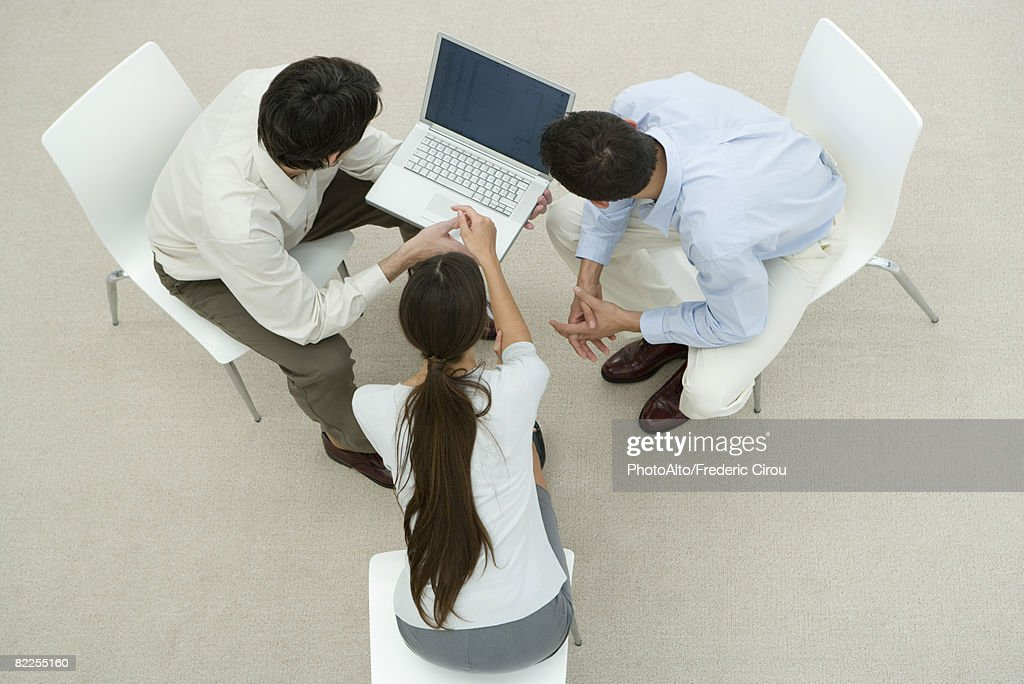Colleagues looking at laptop computer together, overhead view : Stock Photo