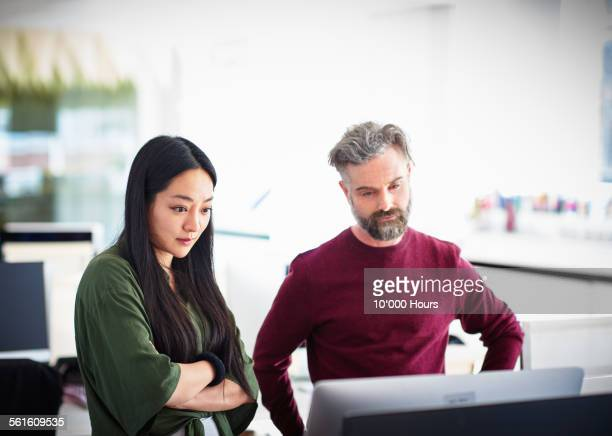 colleagues looking at project on computer screen - leanintogether stock pictures, royalty-free photos & images