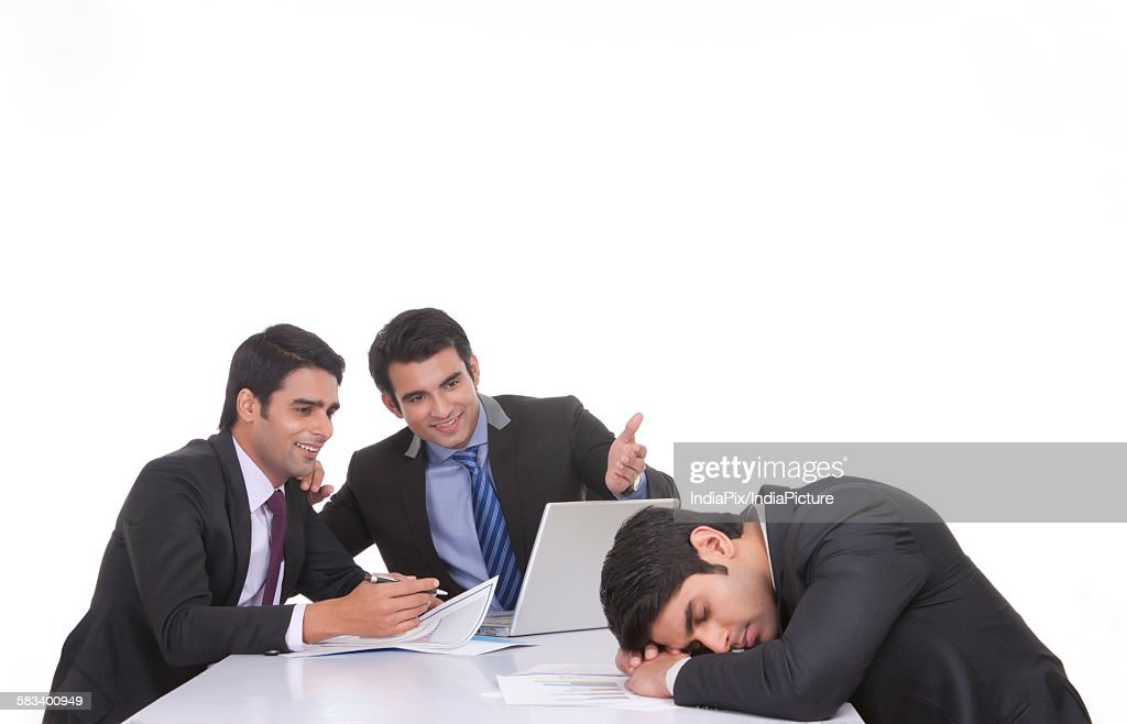 Colleagues making fun of fellow businessman sleeping : Stock Photo