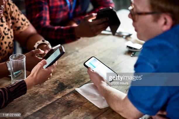 colleagues networking with smart phones - teamevenement stockfoto's en -beelden