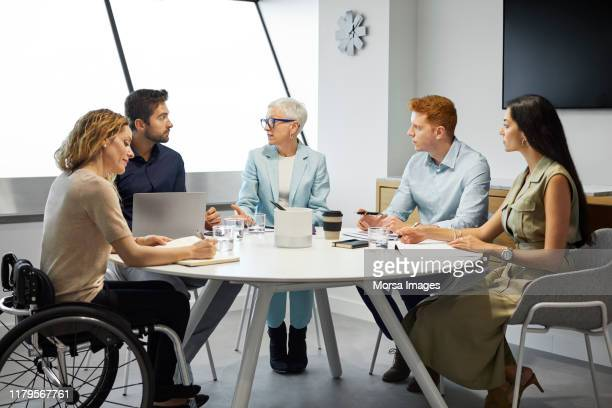 colleagues planning strategy in meeting at office - differing abilities female business stock pictures, royalty-free photos & images