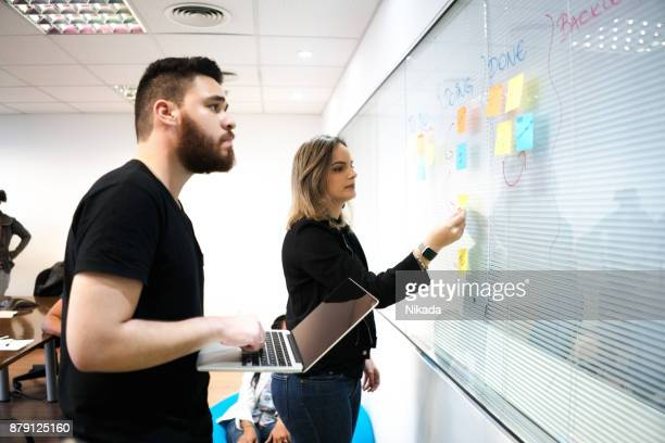 Colleagues planning with adhesive notes and laptop in creative office
