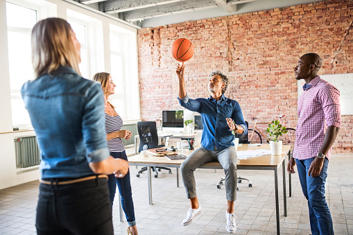 Colleagues playing basketball in office - gettyimageskorea