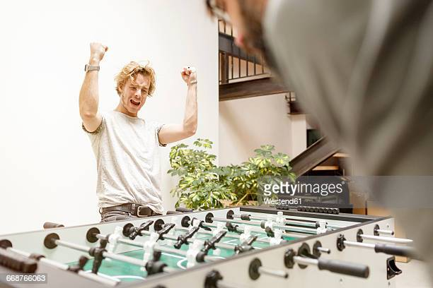 Colleagues playing table football in office