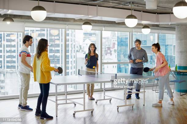 colleagues playing table tennis in office - table tennis stock pictures, royalty-free photos & images