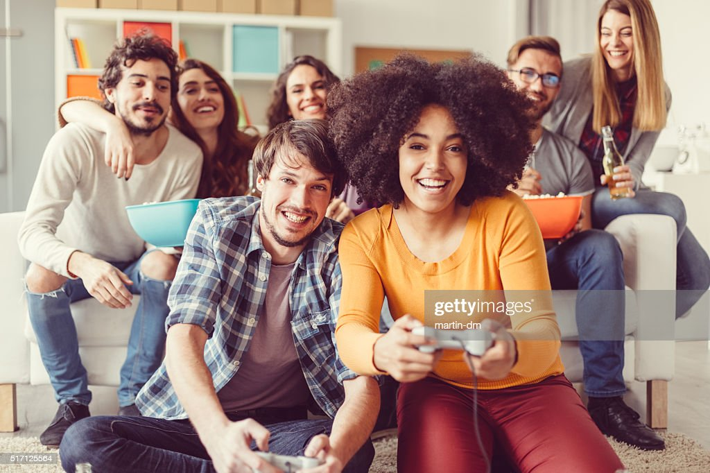 Colleagues playing video games in the office relax room : Stock Photo