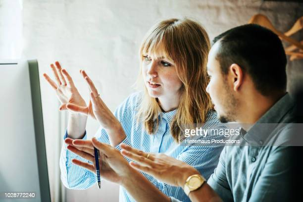 colleagues problem solving at computer together - discussion stock photos and pictures