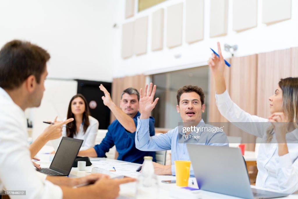 Colegas, levantando a mão, pedindo no encontro de negócios na sala de conferência : Foto de stock