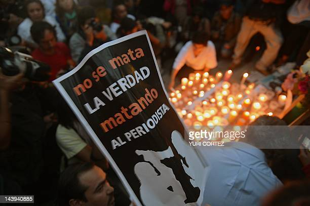 Colleagues relatives and friends of murdered journalists place candles and pictures in an altar erected at the Independence Angel monument in Mexico...