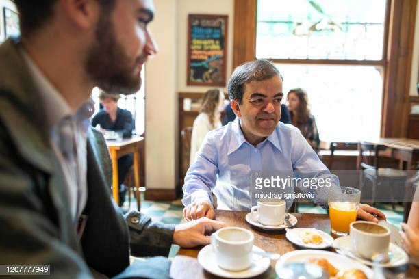 colleagues relaxing after work in cafe - dwarf man stock pictures, royalty-free photos & images