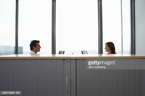Colleagues seated at opposite desks in office, side view
