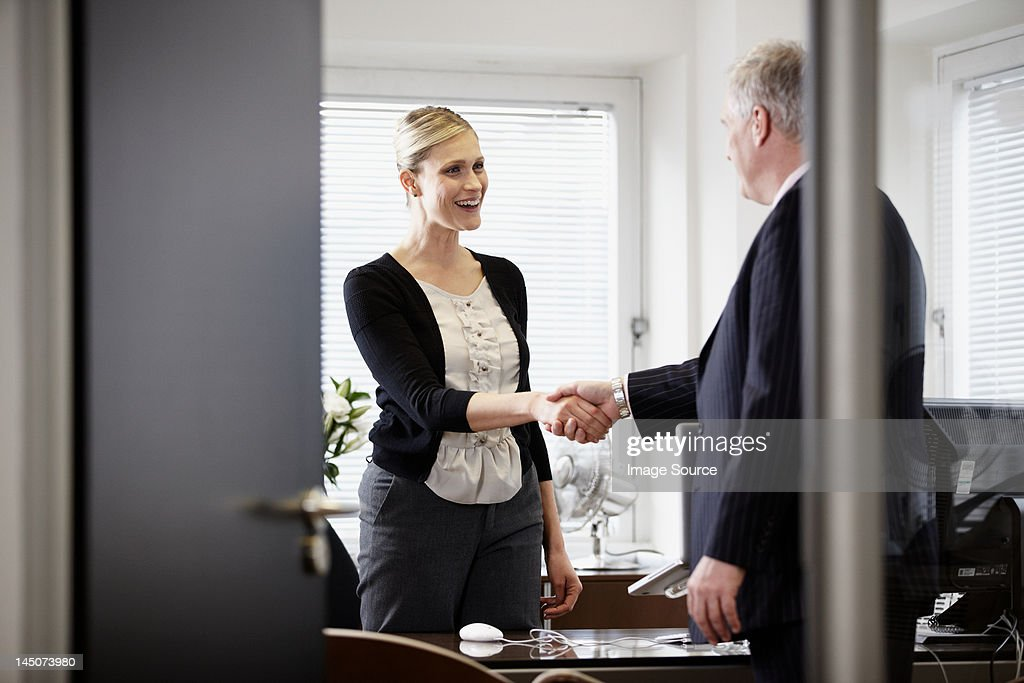Colleagues shaking hands in office : Stock Photo
