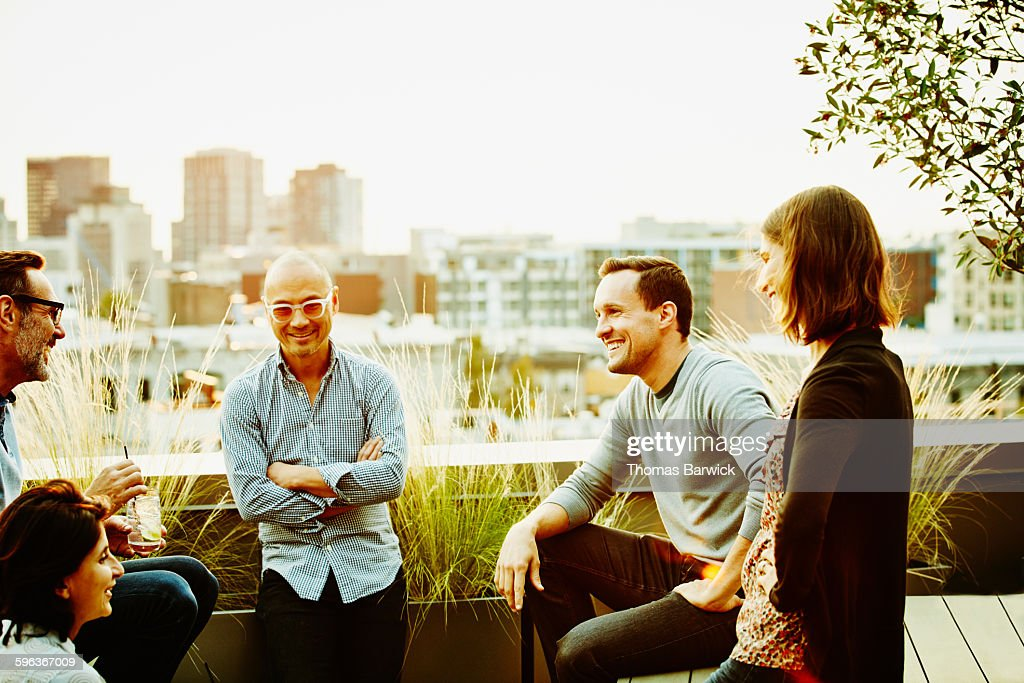 Colleagues sharing drinks on office terrace : Stock Photo