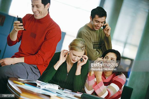 Colleagues sitting around table, using cell phones
