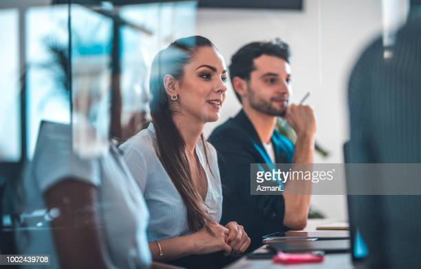Colleagues sitting at conference table in office