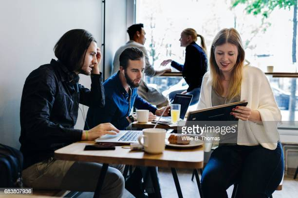 Colleagues Sitting Down, Working In A Business Cafe