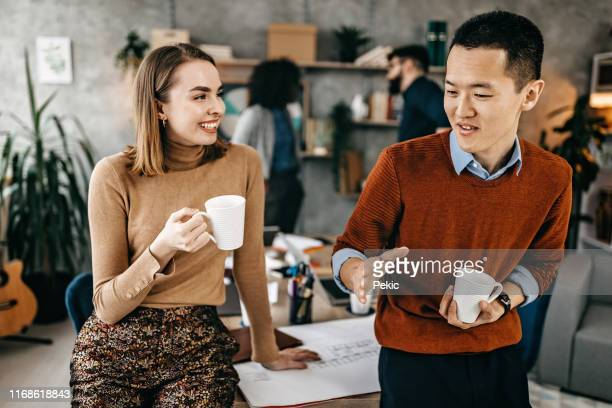 colleagues taking a coffee break at co-working space - coffee break stock pictures, royalty-free photos & images