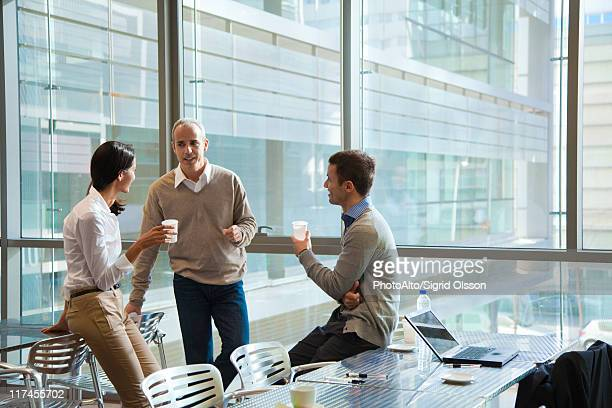 Colleagues taking coffee break in office cafeteria