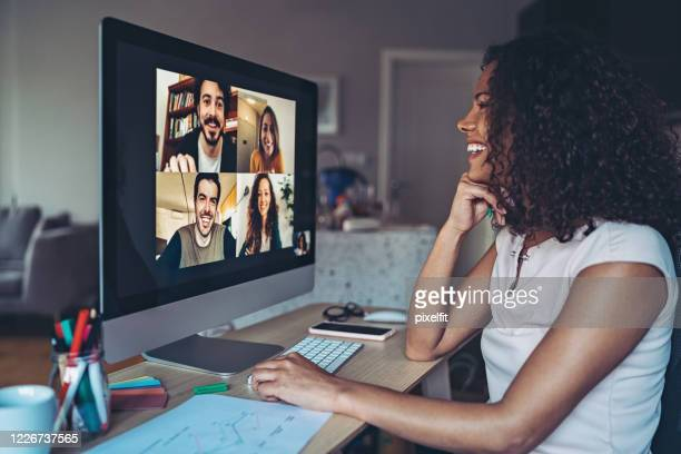 colleagues talk online from their homes - videoconferenza foto e immagini stock