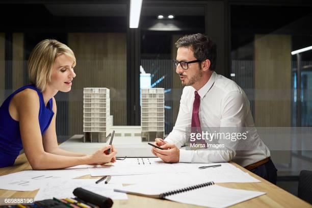 Sus colegas hablando en el escritorio contra la construcción de modelo