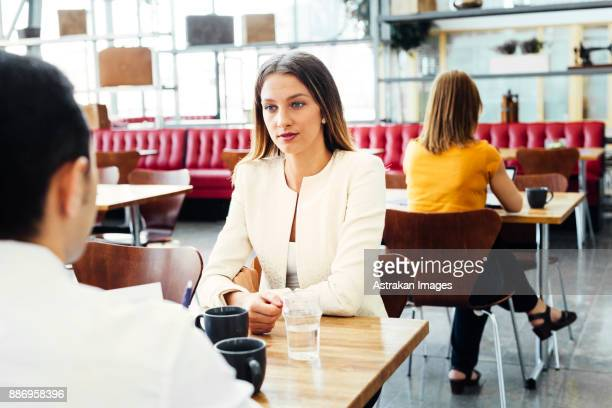 Colleagues talking at table in cafeteria