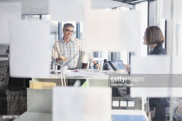 Colleagues talking behind glass wall in office