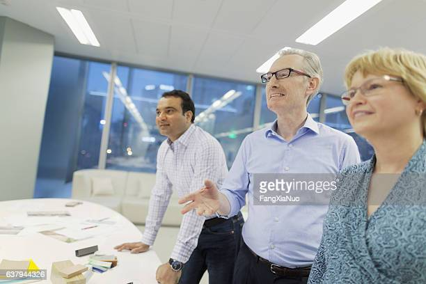 Colleagues talking during presentation in studio office