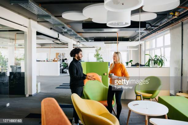 colleagues talking in communal area taking a break - standing stock pictures, royalty-free photos & images