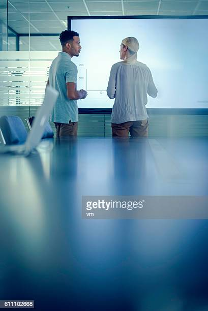 Colleagues talking in front of a projection screen